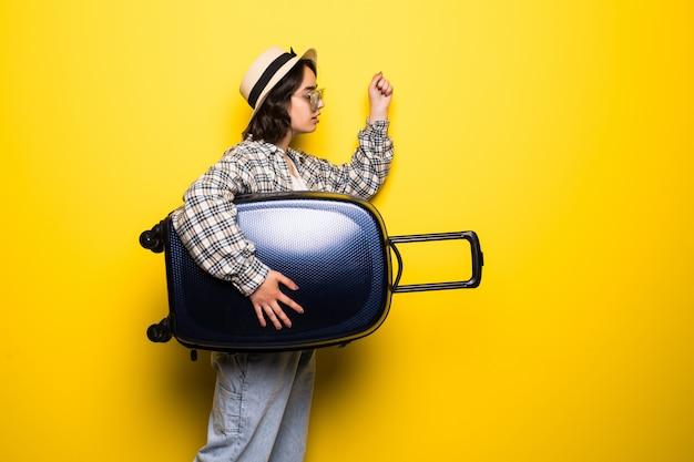 Lächelnde frau, die sonnenbrille und hut mit kofferlauf isoliert trägt