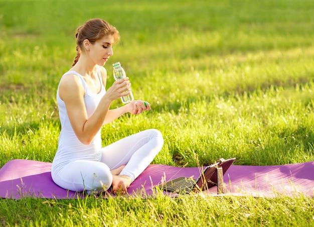 Lächelnde frau, die sportflasche wasser auf yogamatte im park hält