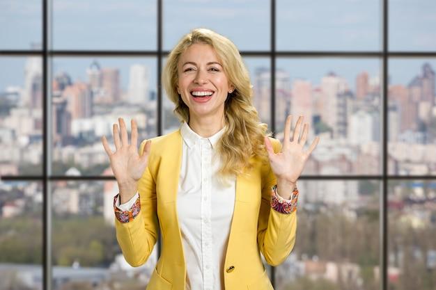 Lächelnde frau, die stoppgeste zeigt. glückliche lächelnde junge geschäftsfrau, die stoppgeste mit beiden händen zeigt, die auf stadt stehen.