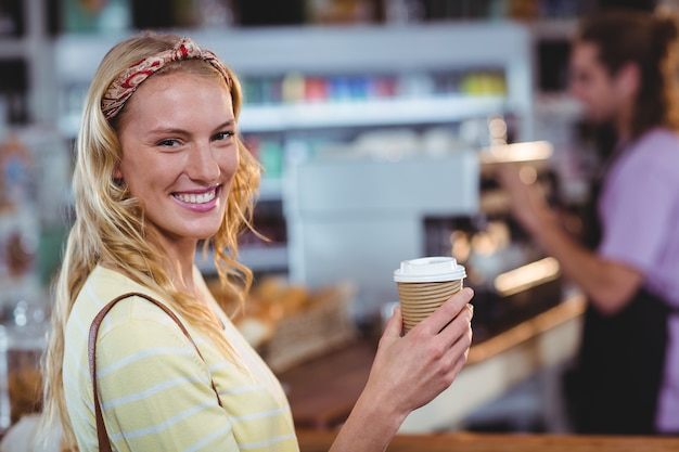 Lächelnde frau, die tasse kaffee hält