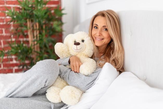 Lächelnde frau, die teddybären hält