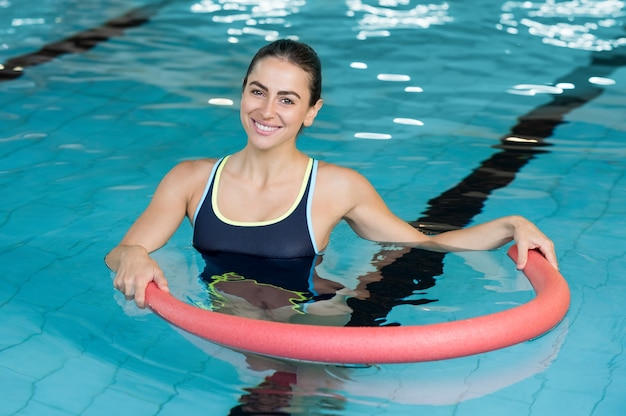 Lächelnde frau, die übung mit aquaröhre in einem schwimmbad tut