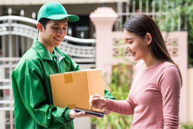 Lächelnde frau, die unterschreibt, erhält eine digitale signatur auf dem smartphone, um eine lieferbox zu akzeptieren