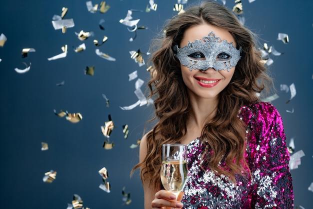 Lächelnde frau, die venetianische karnevalsmaske an der partei über feiertagshintergrund mit lametta trägt