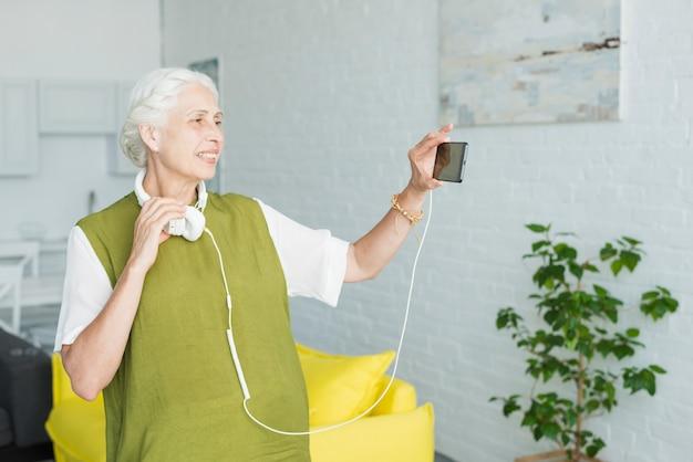 Lächelnde frau, die video auf mobiltelefon mit anhangkopfhörer aufpasst