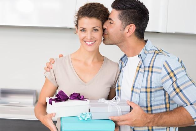 Lächelnde frau, die viele geschenke von ihrem partner hält