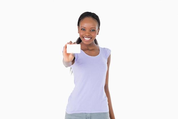 Lächelnde frau, die visitenkarte auf weißem hintergrund darstellt