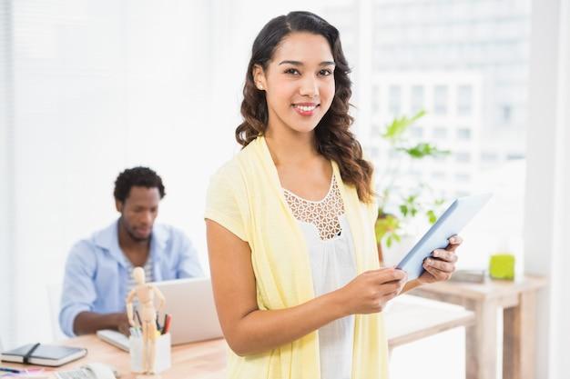 Lächelnde frau, die vor ihrem kollegen mit tablet-computer aufwirft