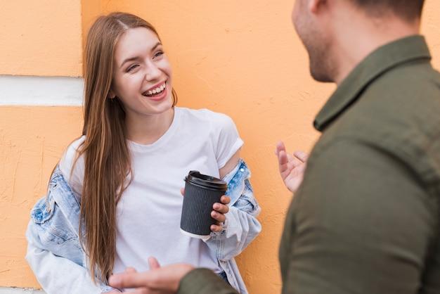 Lächelnde frau, die wegwerfschale bei der unterhaltung mit ihrem freund hält