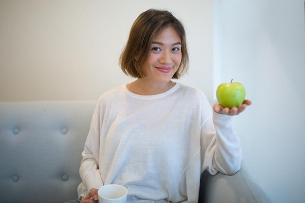 Lächelnde frau, die zu hause grüne apfel- und teeschale hält