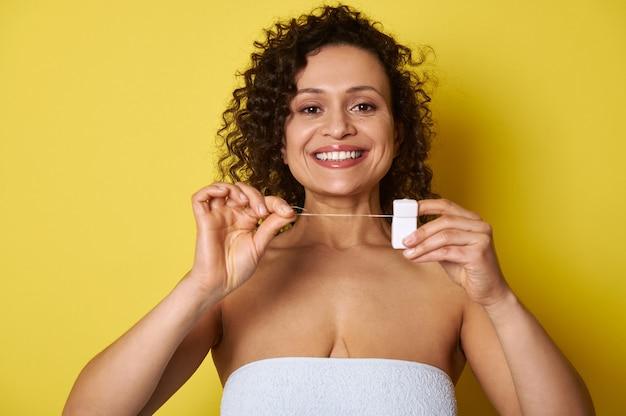 Lächelnde frau, die zur kamera mit zahnseide in ihren händen aufwirft. mund- und zahnpflegekonzepte