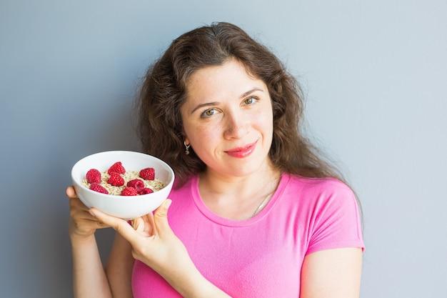 Lächelnde frau hält gesundes und natürliches frühstück, haferflocken und himbeeren in einer schüssel.