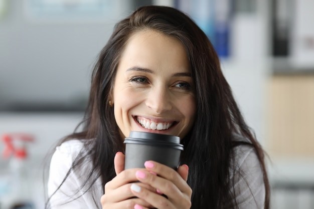 Lächelnde frau hält schwarzen papierbecher