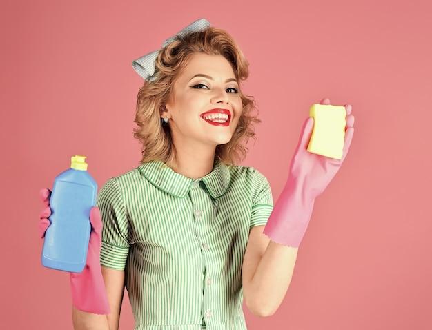 Lächelnde frau hausfrau gekleidet im retro-stil. glückliche haushälterin. retro frauenreiniger. pinup frau halten suppenflasche, staubtuch. aufräumen, reinigungsservice, frau.