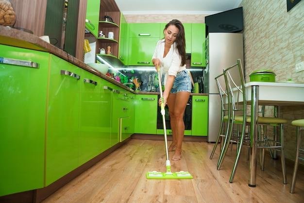 Lächelnde frau hausfrau mit mopp reinigung boden in küche haus reinigung routine kaukasisches mädchen war...