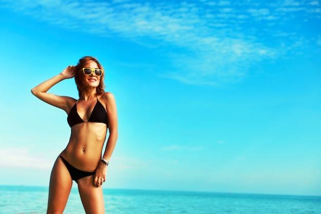 Lächelnde frau im bikini auf den blauen himmel genießen