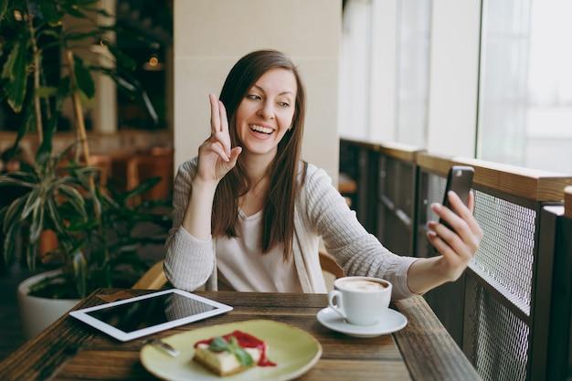 Lächelnde frau im café mit tasse cappuccino, kuchen, selfie auf dem handy, entspannung im restaurant in der freizeit. weibliches sitzen mit pc-tablet-computerrest im café. lifestyle-konzept