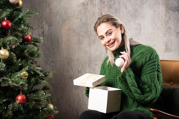 Lächelnde frau im grünen pullover sitzend und posierend mit einer geschenkbox
