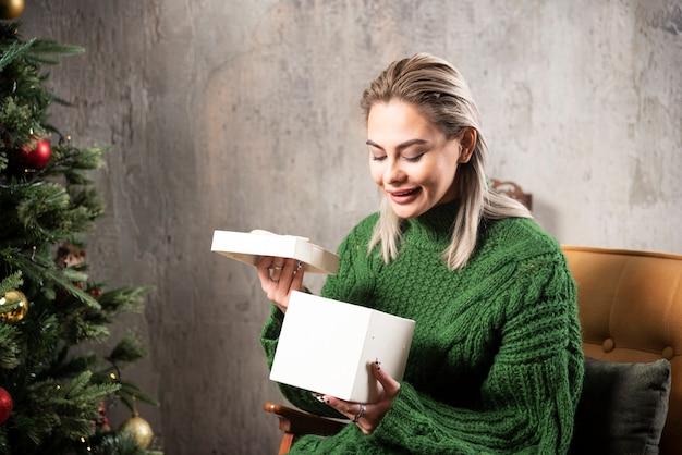 Lächelnde frau im grünen pullover sitzt und öffnet eine geschenkbox