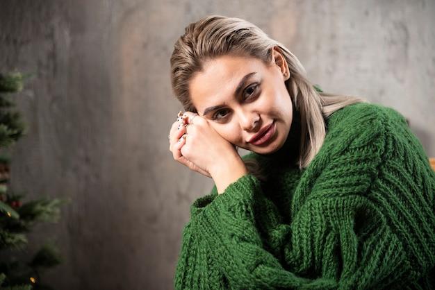 Lächelnde frau im grünen warmen pullover, der auf dem stuhl sitzt und aufwirft