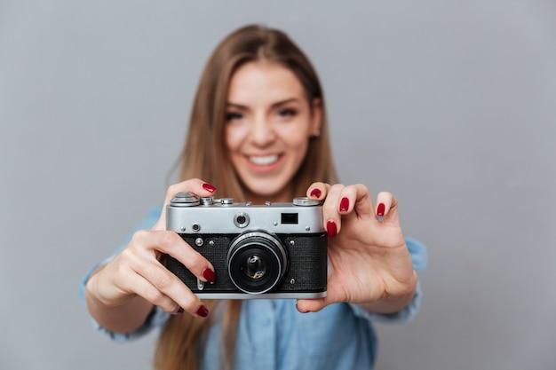 Lächelnde frau im hemd, das telefon auf retro-kamera macht