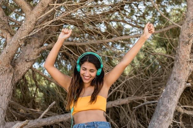 Lächelnde frau im kopfhörer, der spaß hat und musik genießt