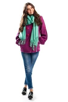 Lächelnde frau im purpurroten mantel. jeanshose und türkisfarbener schal. herbstoutfit mit schwarzen schuhen. kleidung aus baumwolle und fleece.