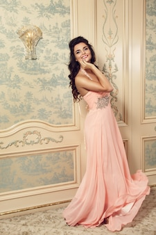 Lächelnde frau im rosa kleid