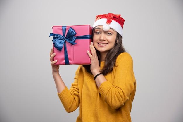 Lächelnde frau im roten hut des weihnachtsmanns mit weihnachtsgeschenk.