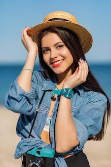 Lächelnde frau im strohhut und im stilvollen sommeroutfit, das mit retro-kamera am strand aufwirft.