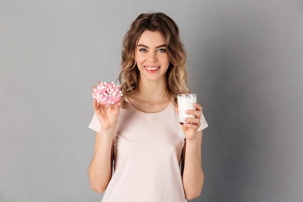 Lächelnde frau im t-shirt, das donut und milch hält, während über grau