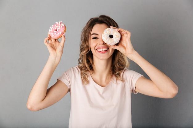 Lächelnde frau im t-shirt, das spaß mit donuts und über grau hat