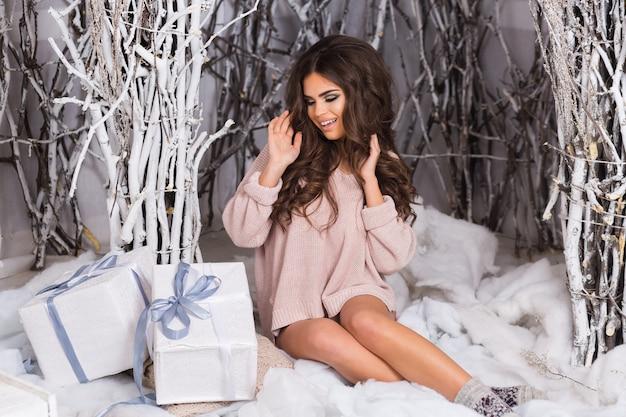 Lächelnde frau im warmen gemütlichen gestrickten rosa pullover, der weiße geschenkbox sitzt sitzend
