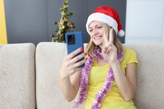 Lächelnde frau im weihnachtsmannhut, der smartphone betrachtet