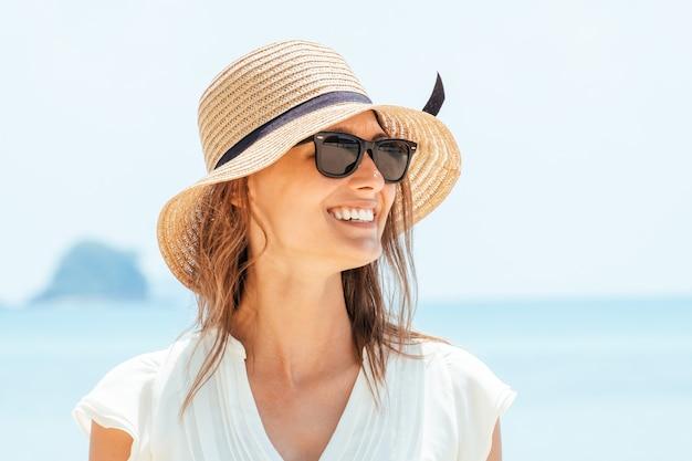 Lächelnde frau im weißen kleid, das auf strand steht