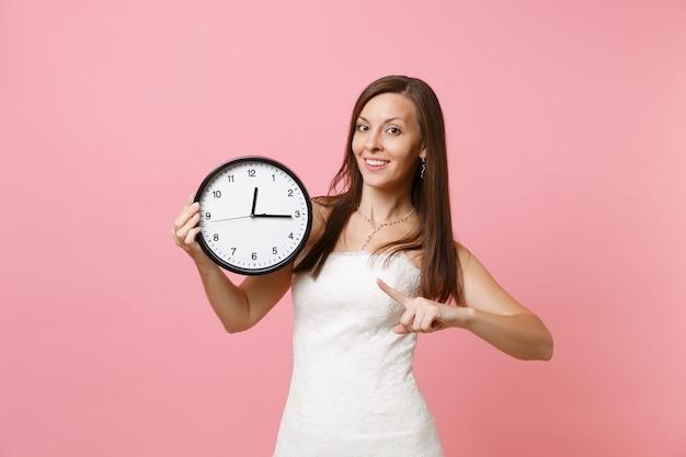 Lächelnde frau im weißen kleid zeigt mit dem zeigefinger auf den runden wecker