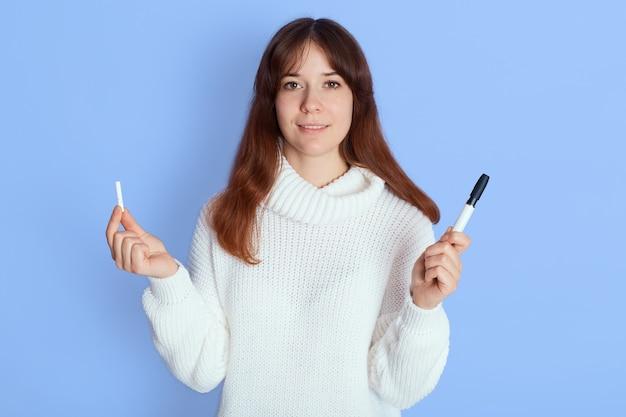 Lächelnde frau im weißen pullover, der über blau steht