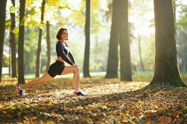 Lächelnde frau in activewear, die beine im park ausdehnt