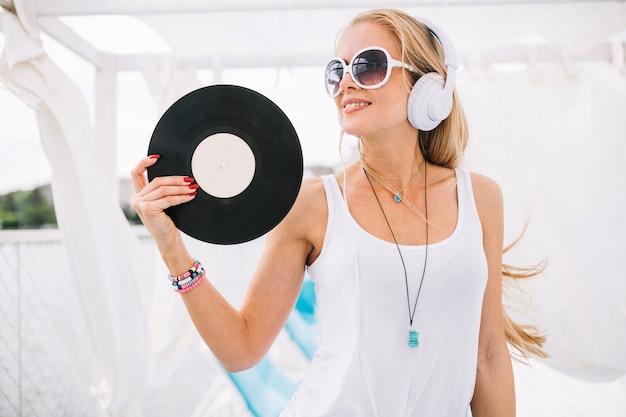 Lächelnde frau in den kopfhörern mit vinyl