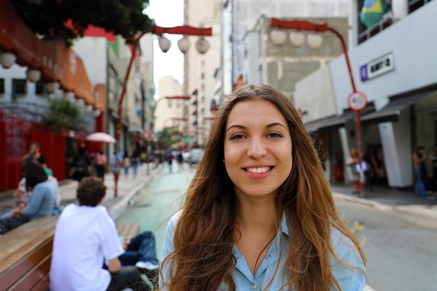 Lächelnde frau in der japanischen nachbarschaft von sao paulo