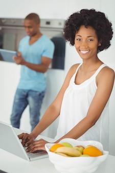 Lächelnde frau in der küche unter verwendung des laptops auf zähler