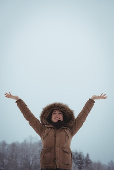 Lächelnde frau in der pelzjacke, die den schneefall genießt
