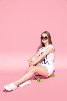 Lächelnde frau in der sonnenbrille auf skateboard