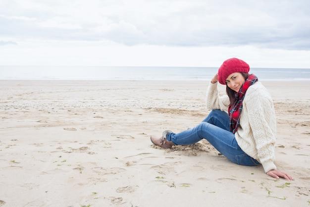 Lächelnde frau in der stilvollen warmen kleidung, die auf strand sitzt