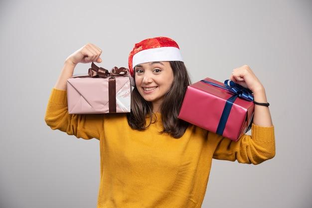 Lächelnde frau in der weihnachtsmannmütze, die geschenkboxen zeigt.
