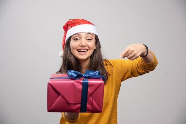 Lächelnde frau in der weihnachtsmütze, die eine geschenkbox zeigt.
