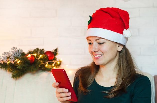 Lächelnde frau in der weihnachtsmütze, die handy am neujahrsfeiertag verwendet.