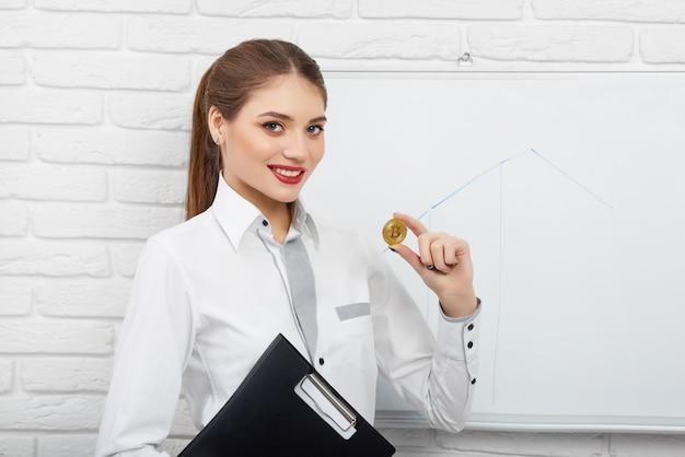 Lächelnde frau in der weißen intelligenten bluse, die kryptowährungs-bitcoin nahe weißer präsentationstafel hält