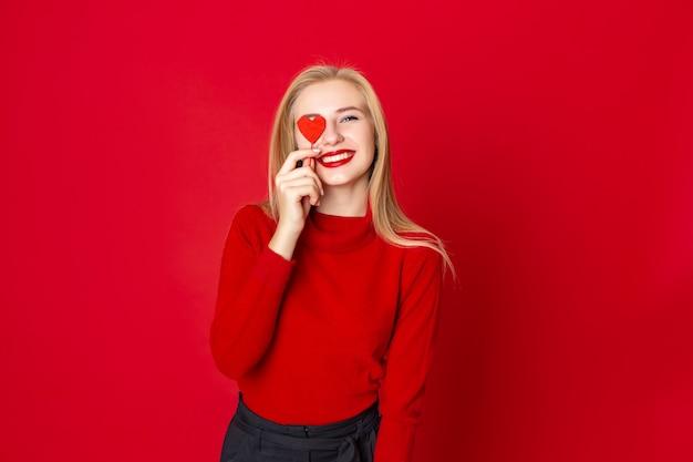 Lächelnde frau in der zufälligen strickjacke über rotem hintergrund