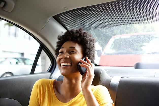 Lächelnde frau in einem auto, das am handy spricht